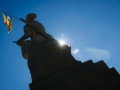 Backlit of El Timbaler del Bruc sculpture in sunny day with a flag on his shoulder, El Burc, Catalonia Spain